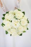 Huwelijksboeket met vele witte rozen in handen royalty-vrije stock foto's