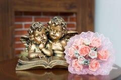 Huwelijksboeket naast de engelen en de open haard Royalty-vrije Stock Foto's