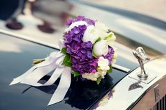 Huwelijksboeket op een huwelijksauto Stock Fotografie