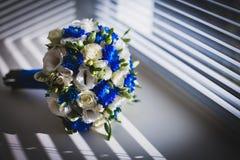 Huwelijksboeket op het venster met zonneblinden de attributen van de bruidegom Onlangs echtpaar stock fotografie
