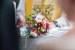 Huwelijksboeket op lijst tussen bruid en bruidegom stock fotografie