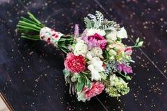 Huwelijksboeket van anjers en rozen, op een houten lijst Stock Foto's