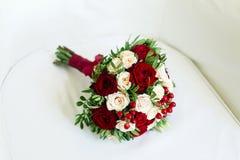 Huwelijksboeket van anjers en rozen, op een witte stoel Stock Foto