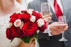 Huwelijksboeket van rode en witte rozen in de hand van de bruid en een glas champagne in de andere hand stock foto