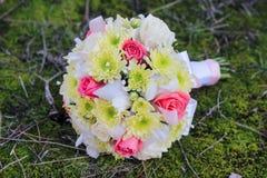 Huwelijksboeket van roze, chrysant, iris, en gypsophila op het bosmos Stock Afbeeldingen