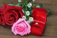 Huwelijksboeket van roze en rode rozen, Trouwring in een rode doos op houten achtergrond stock foto's