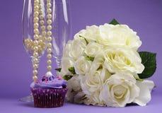Huwelijksboeket van witte rozen met purpere cupcake en parels in champagneglas Royalty-vrije Stock Foto's