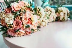 Huwelijksboeketten van bruid en bruidsmeisjes op lijst vóór ceremo Stock Foto's