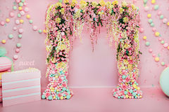 Huwelijksboog binnen Feestelijke decoratie met bloemen en kleurrijke ballons op roze achtergrond stock fotografie