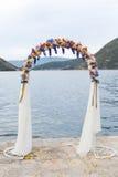 Huwelijksboog met bloemen in openlucht wordt verfraaid die Stock Afbeelding