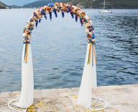 Huwelijksboog met bloemen in openlucht wordt verfraaid die Stock Foto's