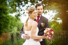 Huwelijksbruid en bruidegom in een weide Stock Afbeeldingen
