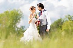 Huwelijksbruid en bruidegom in een weide, met bruids boeket Stock Foto
