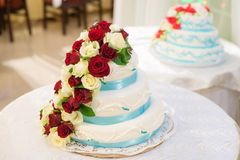 Huwelijkscake die met rode en witte bloemenrozen wordt verfraaid op witte achtergrond royalty-vrije stock afbeeldingen