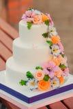 Huwelijkscake met suikerbloemen die wordt verfraaid Royalty-vrije Stock Fotografie