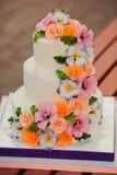 Huwelijkscake met suikerbloemen die wordt verfraaid Stock Foto