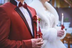 Huwelijksceremonie die in kerk, jong echtpaar de kaarsen, christelijke tradities houden Stock Foto's