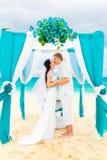 Huwelijksceremonie op een tropisch strand in blauw Gelukkige bruidegom en br stock foto