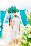 Huwelijksceremonie op een tropisch strand in blauw Gelukkige bruidegom en br Stock Afbeeldingen
