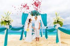 Huwelijksceremonie op een tropisch strand in blauw Gelukkige bruidegom en br Royalty-vrije Stock Afbeeldingen