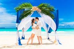 Huwelijksceremonie op een tropisch strand in blauw Gelukkige bruidegom en br Stock Fotografie