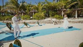 Huwelijksceremonie op een tropisch strand onder palmen en de oceaan De bruid komt plechtig aan hem Het schieten in motie stock video