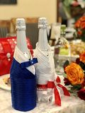 Huwelijksdecor: de oranje en rode rozen, glazen, flessen, schouwt de jonggehuwden van de lijstdecoratie, Presidium stock fotografie