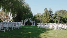 Huwelijksdecoratie met boog en witte stoelen stock video