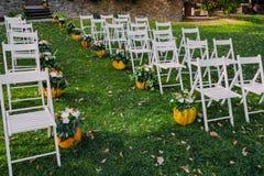 Huwelijksdecoratie met de herfstpompoenen en bloemen Ceremonie openlucht in het park Witte stoelen voor gasten Stock Fotografie