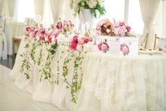 Huwelijksdecoratie op lijst Violette bloemen Bloemenregelingen en decoratie Regeling van roze en witte bloemen in restaurant voor Stock Foto's