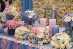 Huwelijksdecoratie van bloemen en kaarsen op de lijst in een restaurant Stock Afbeeldingen