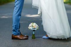 Huwelijksdetails: klassieke bruine en blauwe schoenen van bruid en bruidegom Boeket van rozen die zich op de grond tussen hen bev Stock Fotografie