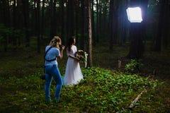 Huwelijksfotograaf die stroboscoop met behulp van en softbox om close-upportretten te maken stock afbeeldingen