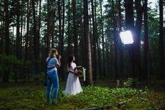 Huwelijksfotograaf die stroboscoop met behulp van en softbox om close-upportretten te maken royalty-vrije stock fotografie