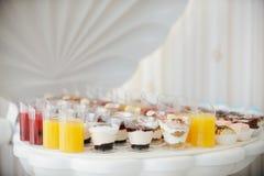 Huwelijksfourchette met multi gekleurde drank, gekleurde pastelkleur cupcakes, schuimgebakjes Elegante en luxueuze gebeurtenisreg royalty-vrije stock afbeeldingen