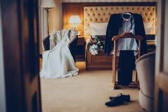 Huwelijkskleding, kostuum en boeket in de hotelruimte stock foto
