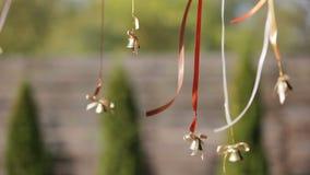 Huwelijksklokken die op linten in de wind hangen stock footage