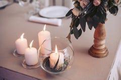 Huwelijkslijst met kaarsen en een boeket van bloemen in zachte kleuren Royalty-vrije Stock Foto