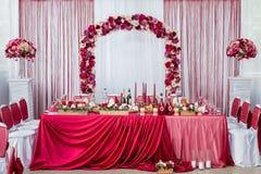 Huwelijkslijst voor de jonggehuwden verfraaid met verse bloemen en een rood tafelkleed royalty-vrije stock fotografie