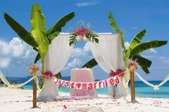 Huwelijksopstelling en bloemen op tropische strandachtergrond Stock Fotografie