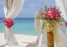 Huwelijksopstelling en bloemen op tropische strandachtergrond Stock Foto