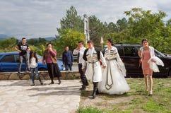 Huwelijksoptocht met de bruid en de bruidegom die pret in de Georgische stijl gaan hebben Stock Foto's