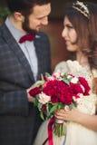 Huwelijkspaar die, de bruid die een boeket van bloemen in haar hand, bruidegom het omhelzen houden koesteren Royalty-vrije Stock Fotografie