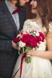 Huwelijkspaar die, de bruid die een boeket van bloemen in haar hand, bruidegom het omhelzen houden koesteren Royalty-vrije Stock Foto's