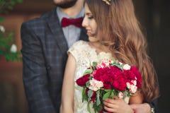 Huwelijkspaar die, de bruid die een boeket van bloemen in haar hand, bruidegom het omhelzen houden koesteren Royalty-vrije Stock Afbeeldingen
