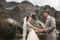 Huwelijkspaar die en handen op de meerkust lopen houden Zonnige dag in Tatra-Bergen royalty-vrije stock foto's