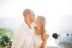Huwelijkspaar die en op rotsen dichtbij blauwe overzees kussen koesteren Royalty-vrije Stock Afbeeldingen