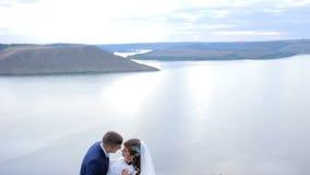 Huwelijkspaar die teder op de berg piekrand kussen met verbazende mening stock videobeelden