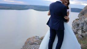 Huwelijkspaar die teder op de berg piekrand kussen met verbazende mening stock footage