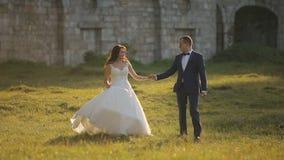 Huwelijkspaar die vóór Kasteel lopen stock footage